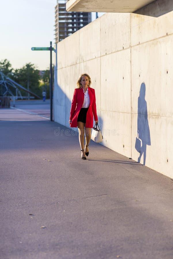穿红色夹克,裙子和拿着一个白色提包的一名端庄的妇女的正面图,当走在街道在一好日子时 免版税图库摄影