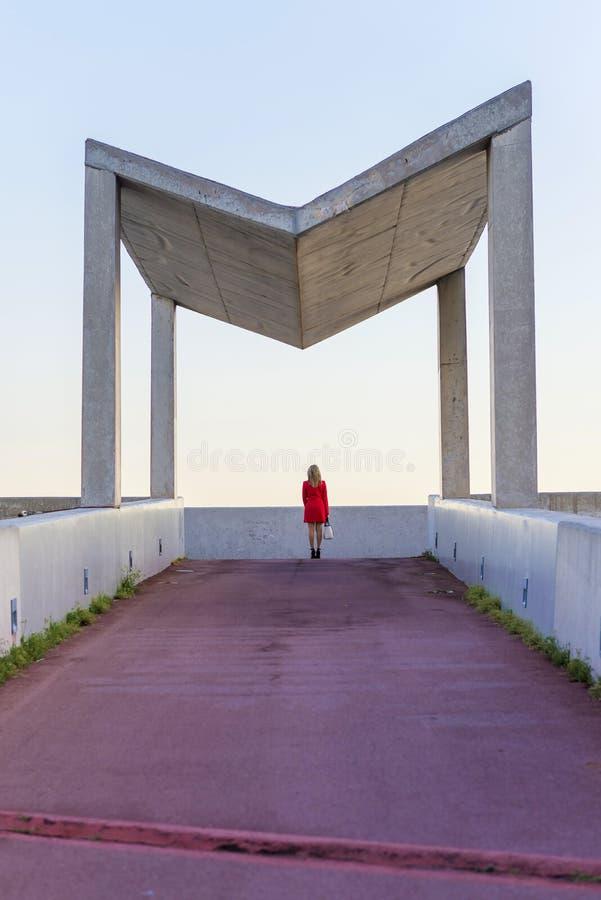 穿红色夹克,裙子和拿着一个白色提包的一名端庄的妇女的背面图,当站立在街道在一好日子时 库存图片