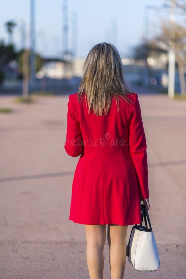 穿红色夹克,裙子和拿着一个白色提包的一名端庄的妇女的背面图,当走在街道在一好日子时 库存照片