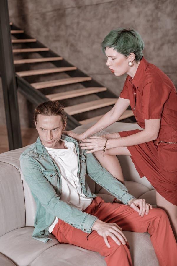 穿红色礼服的绿发的妇女尖叫对她的男朋友 免版税库存图片