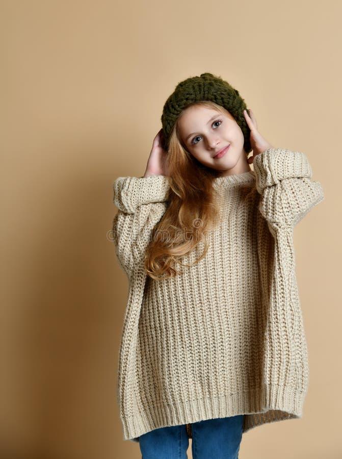 穿被编织的帽子和毛线衣的愉快的女孩冬天画象 免版税图库摄影