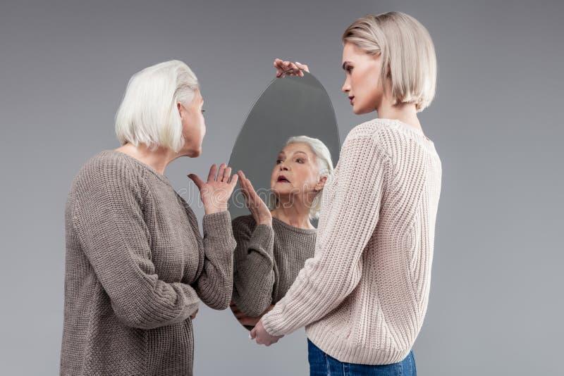 穿被编织的灰色毛线衣和检查出现的俏丽的老妇人 库存照片