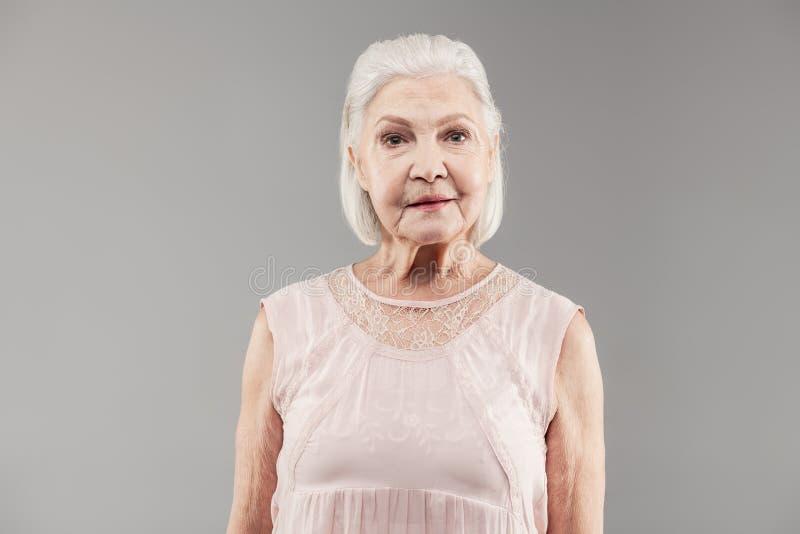穿轻的丝绸女衬衫的短发老妇人,当摆在时 库存图片