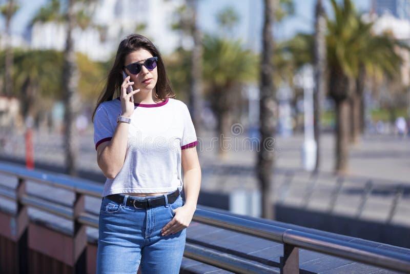 穿都市衣裳的一美丽的年轻女人的正面图走在街道,当使用一个手机户外在明亮时 免版税库存图片