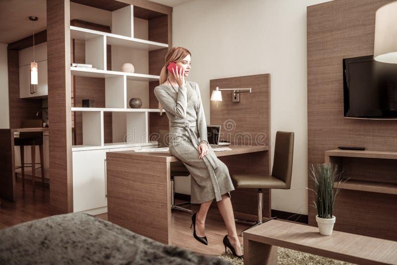 穿长的礼服和高跟鞋的亭亭玉立的女实业家 免版税库存照片