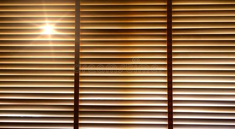 窗帘,在木窗帘之外的太阳光,阳光和阴影在窗帘 免版税库存照片
