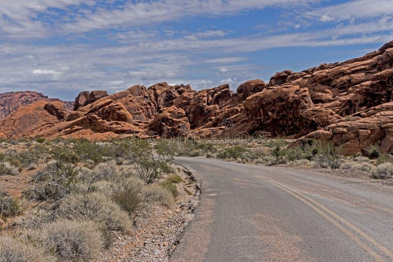 窄路导致火谷的被绘的岩层  免版税库存照片