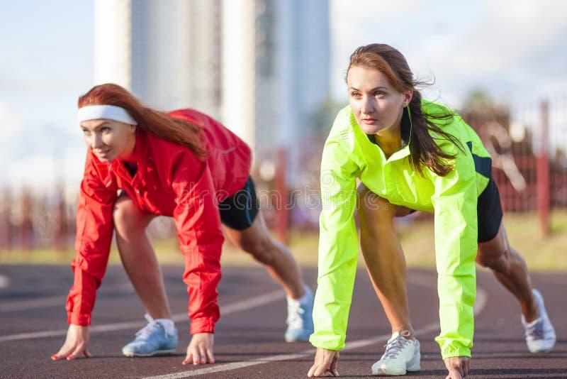 站立两位白种人的运动员为跑在轨道路线做准备 免版税库存图片