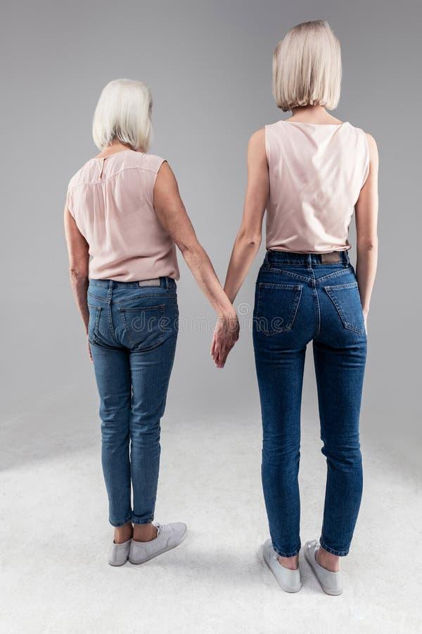 站立与她的老母亲和握她的手的白肤金发的短发女孩 库存照片