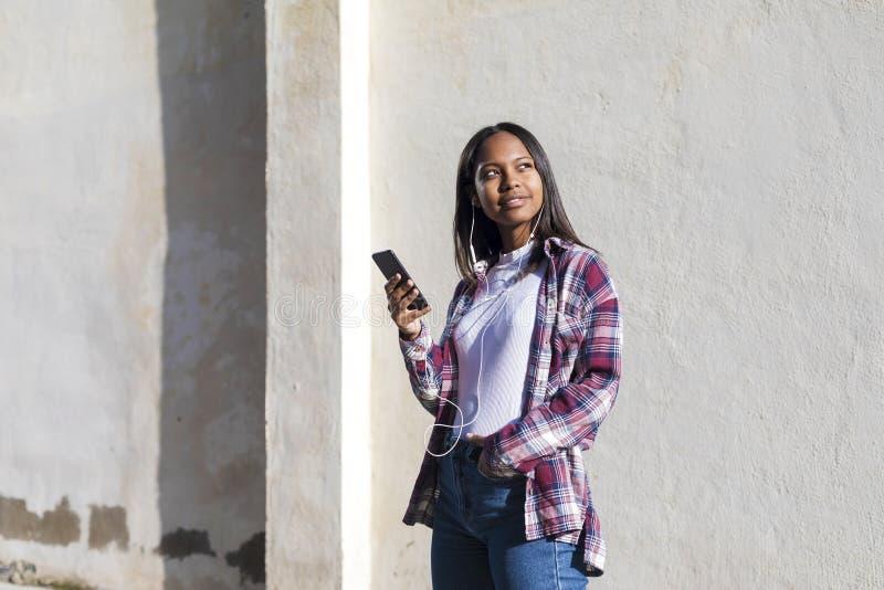 站立一名年轻微笑的非裔美国人的妇女的正面图户外,当微笑和听的音乐由在晴朗时的耳机 库存图片