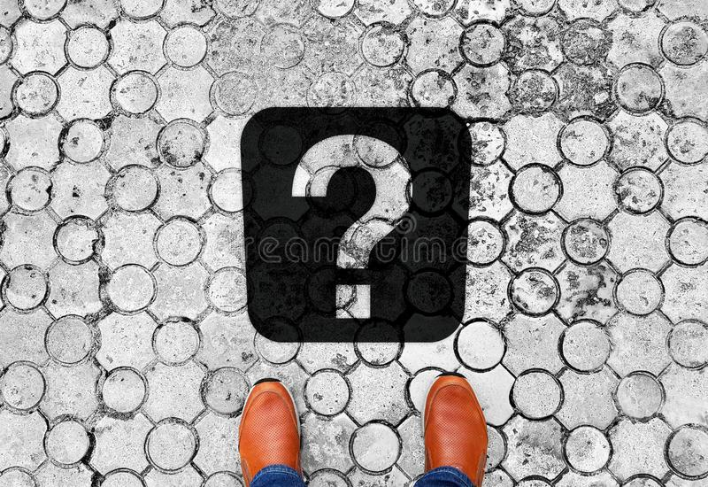 站立在与问号-人生的下个旅行目的地的意思的地板上的布朗鞋子 库存图片
