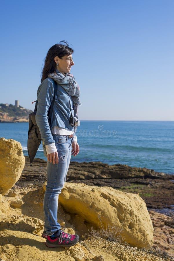 站立在海滨的一作白日梦的年轻女人佩带的便服的侧视图,当看对在明亮时的天际 免版税库存照片