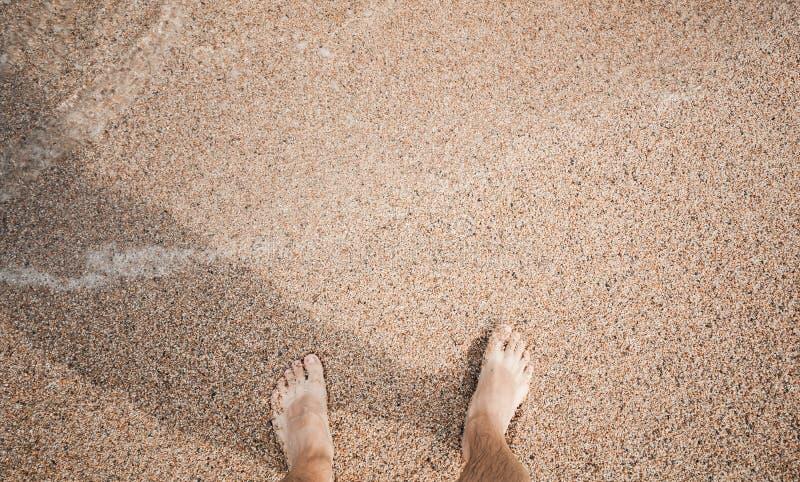 站立在海滩的赤足男性腿 免版税图库摄影