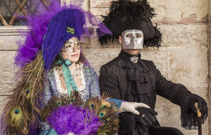 站立在窗口下的威尼斯式狂欢节面具夫妇  库存图片