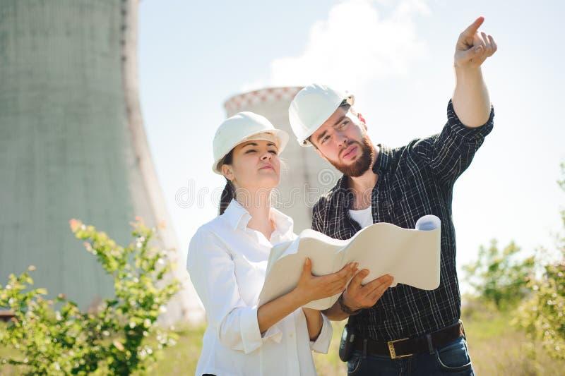 站立在电驻地的两位工程师,谈论计划 库存图片