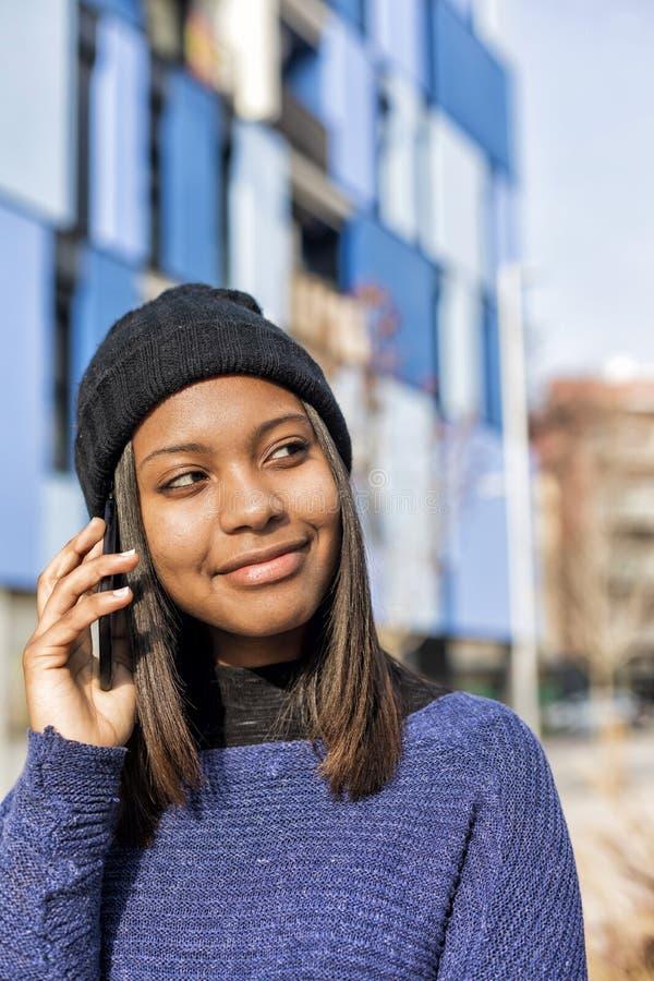 站立户外和打电话的一名快乐的年轻非洲妇女的画象,当看时 免版税库存照片