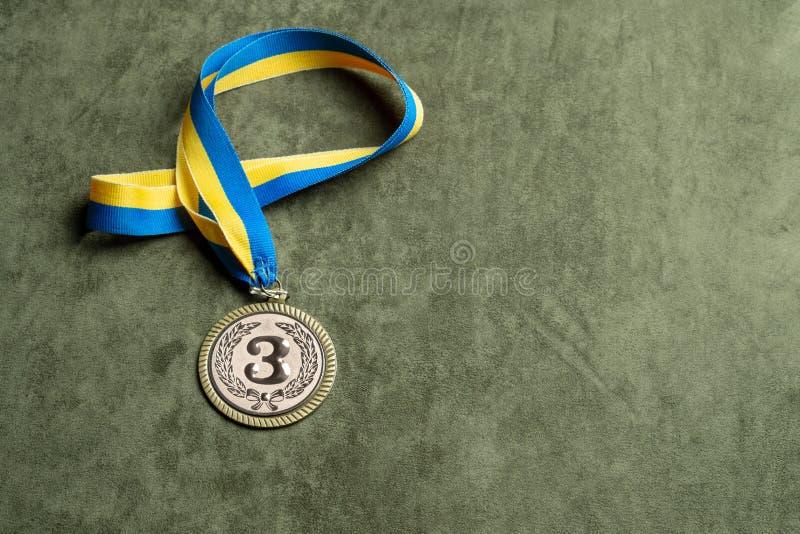 第三名的铜牌与黄色蓝色丝带,拷贝空间 库存照片