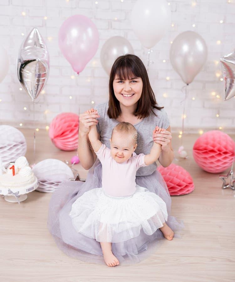 第一个生日概念-坐与母亲的可爱宝贝女孩在装饰的屋子里 免版税库存图片