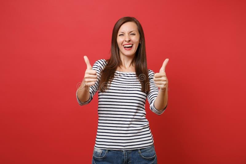 笑在明亮的红色偶然镶边衣裳的愉快的年轻女人画象站立和显示赞许隔绝的 免版税库存照片