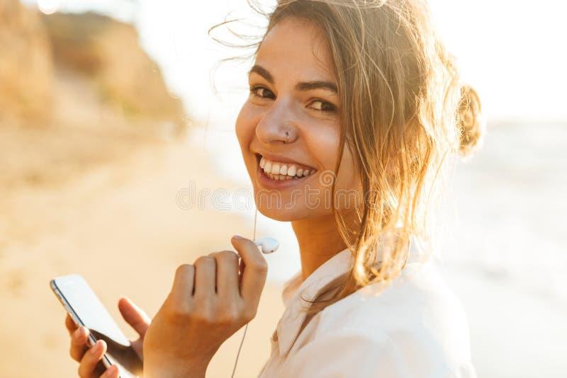 笑和使用手机的可爱的女孩20s的图象,当走由海边时 免版税库存图片