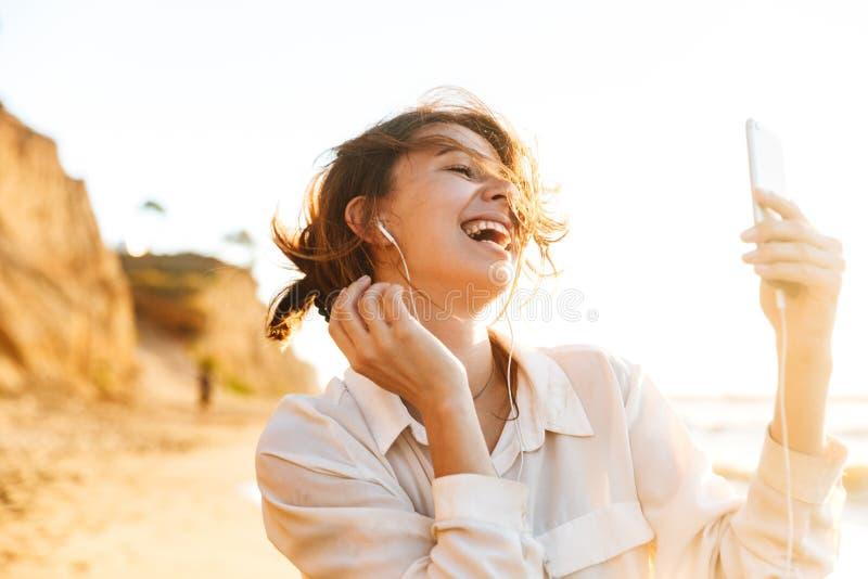 笑和使用手机的欧洲女孩20s佩带的耳机的图象,当走由海边时 免版税图库摄影