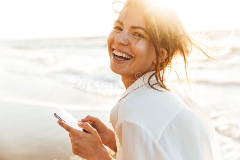 笑和使用手机的美女20s的图象,当走由海边时 库存照片