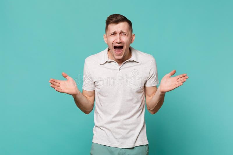 笑站立的便服的,在蓝色绿松石墙壁上隔绝的传播的手傻笑的年轻人画象  图库摄影