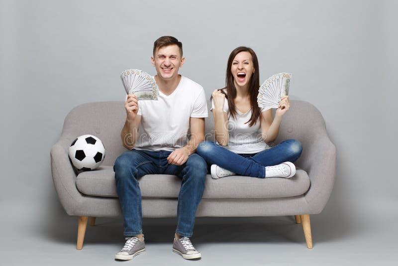 笑的夫妇妇女人足球迷在美元钞票欢呼金钱,现金支持喜爱的队藏品爱好者  库存照片
