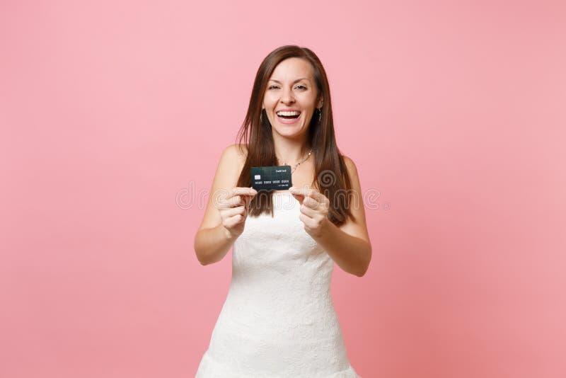 笑的新娘妇女画象显示在照相机的白色婚纱的信用卡在桃红色淡色背景 免版税图库摄影