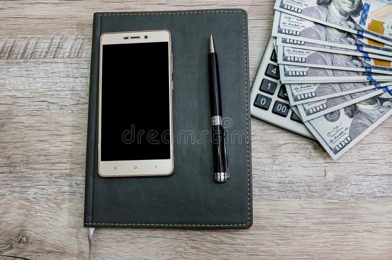 笔记本、笔、智能手机、计算器和美元在木背景 免版税库存图片