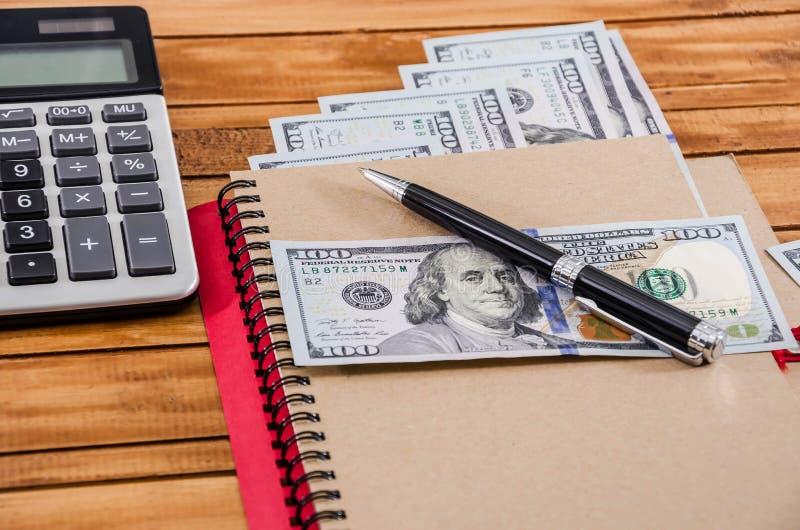 笔记本、笔、美元和一个计算器在木背景 免版税图库摄影