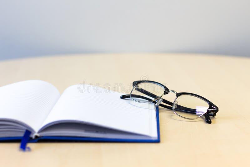 笔记本开放与在木桌上的玻璃 免版税库存照片