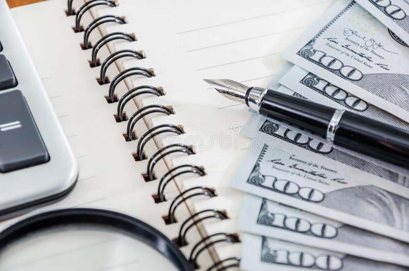 笔记薄、笔、放大器、计算器和美元 免版税库存图片