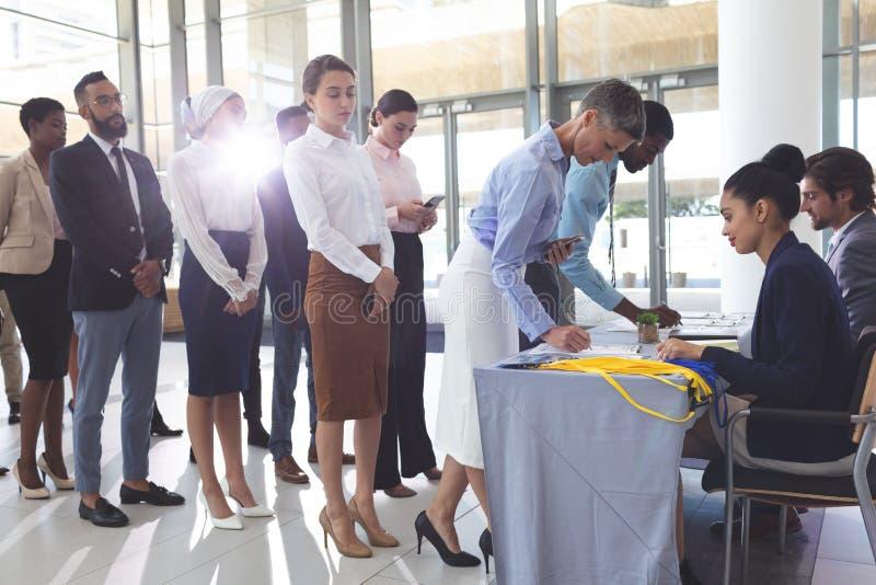 签到在会议注册桌上的女实业家和商人 免版税库存图片