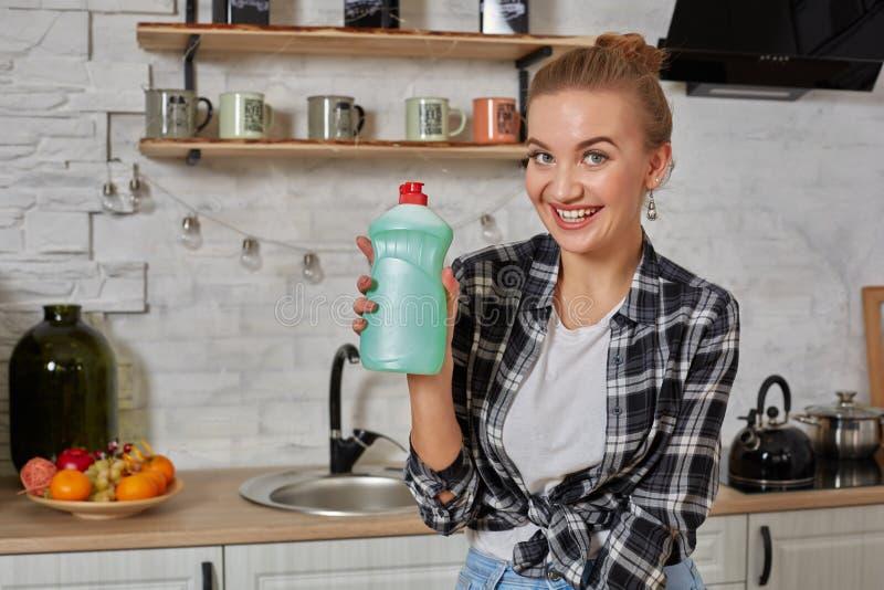 管家妇女有擦净剂液体的藏品瓶 瓶拷贝空间 免版税库存图片