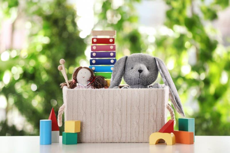 箱子和不同的玩具在桌上 免版税库存图片