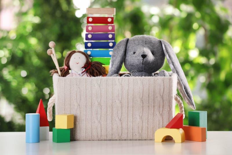 箱子和不同的玩具在桌上 库存图片
