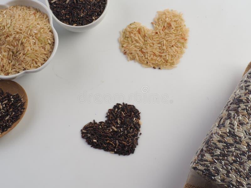 米的重点 有机糙米和米莓果在白色背景 图库摄影