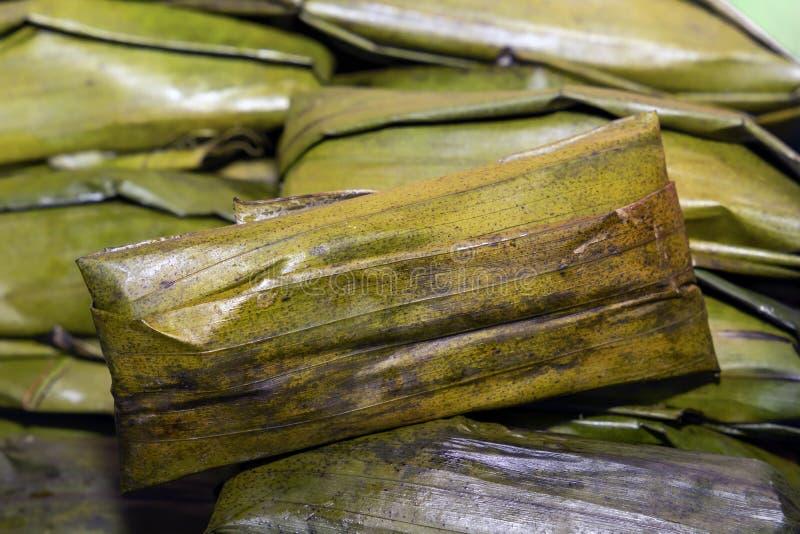 米金字塔-与在棕榈叶包裹的各种各样的添加剂的煮沸的米-传统亚洲街道食物 免版税库存照片