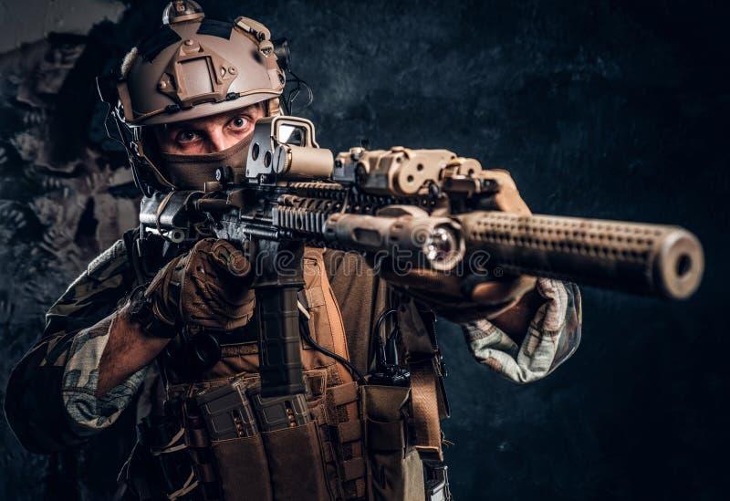 精华单位,拿着有激光的伪装制服的特种部队战士一杆攻击步枪看见并且瞄准 免版税库存照片