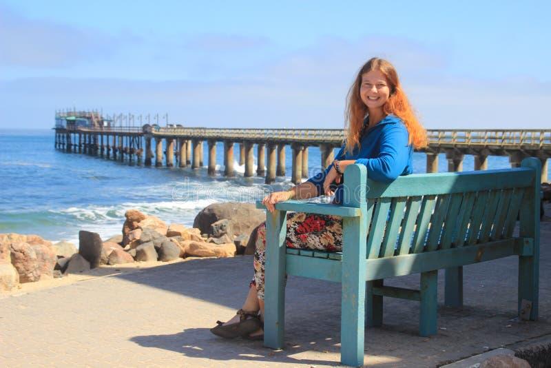 红发愉快的白白种人女孩坐在大西洋的岸的一条长凳在斯瓦科普蒙德纳米比亚和笑 库存照片