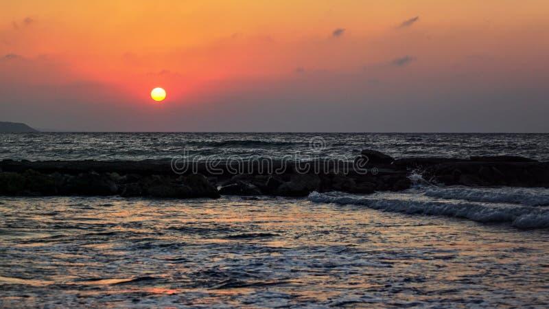 红色太阳在风平浪静的晚上发光在海滩,天空附近是好的日落颜色 免版税库存图片