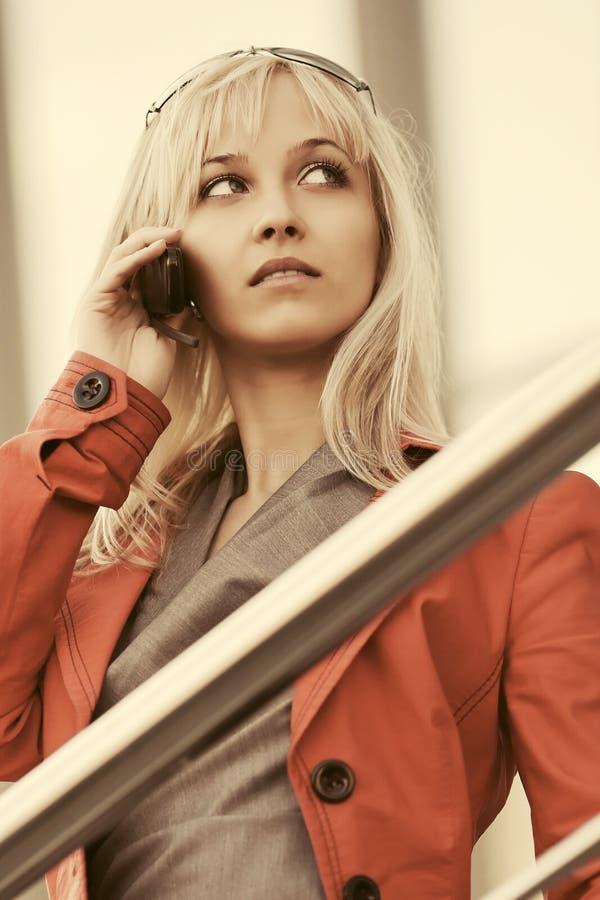 红色夹克的年轻白肤金发的时装业妇女拜访手机的 免版税库存照片
