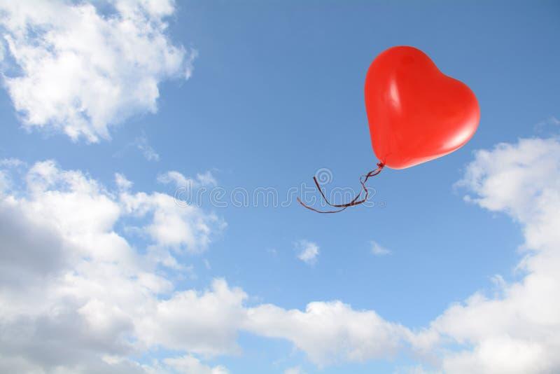 红色心形的气球飞行入与云彩的天空蔚蓝,爱概念,拷贝空间 免版税库存照片