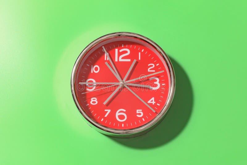 红色圆的时钟用有大白色数字的很大数量的手在绿色背景 库存图片