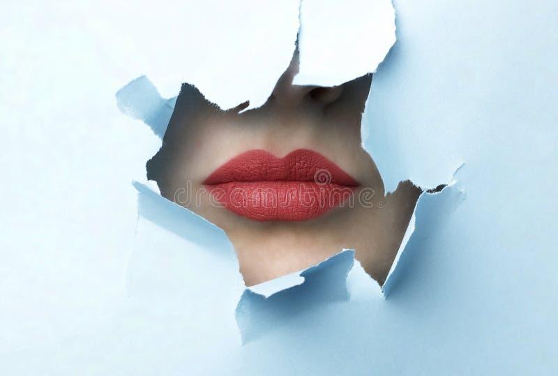 红色嘴唇和蓝色被撕毁的纸背景 库存图片