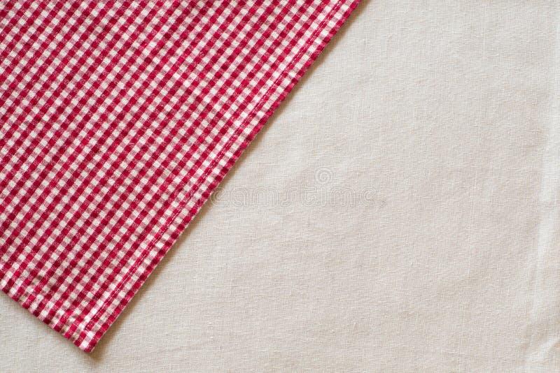 红色和白色被检查的布料在白色或米黄色的亚麻制桌布的上部角落的角度 水平的上面看法与 免版税库存图片