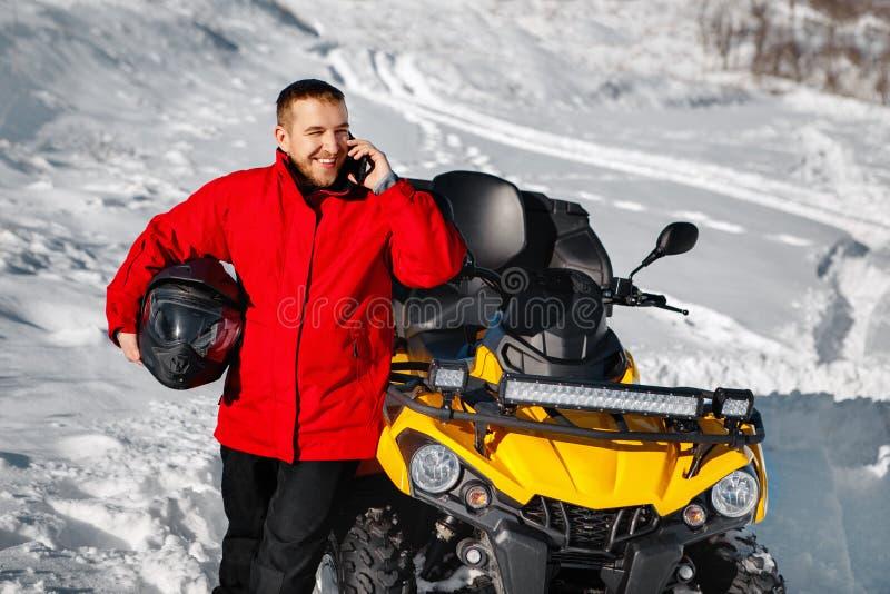 红色温暖的冬季衣服和黑盔甲的年轻人司机谈话在智能手机在ATV 4wd方形字体自行车立场附近  库存图片