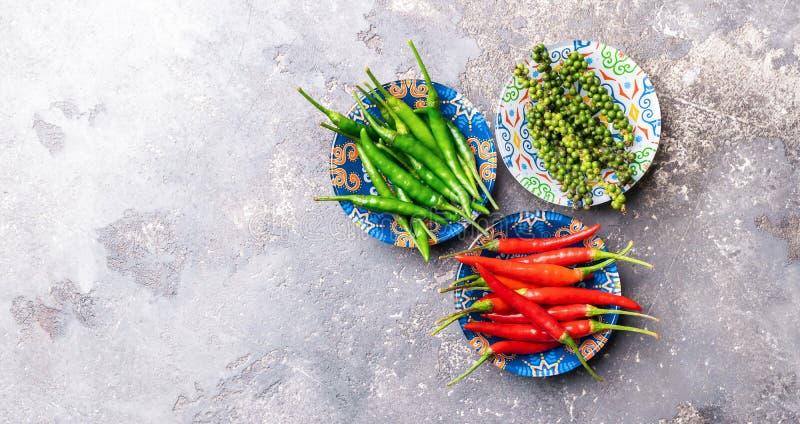 红色绿色黑色的各种各样的类型胡椒在一个碗的有在灰色背景的五颜六色的装饰品的 平的布局 免版税图库摄影