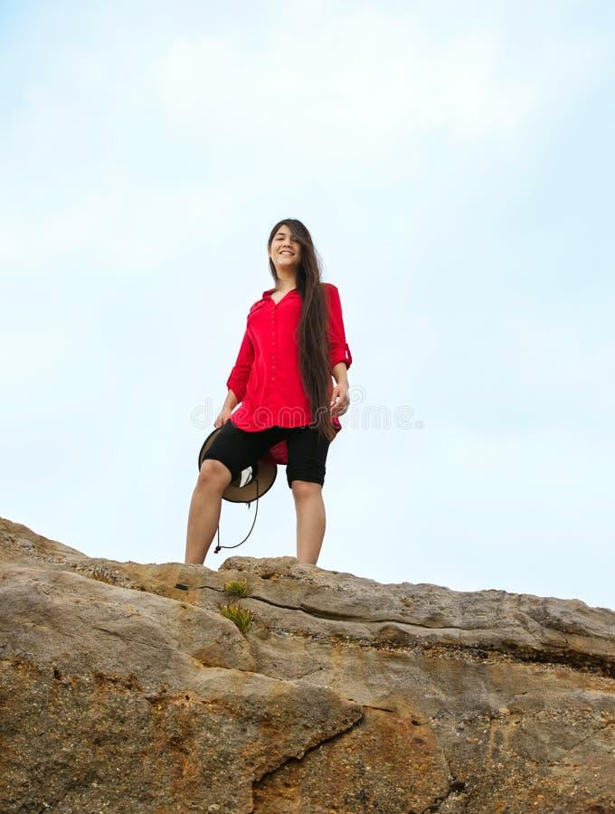 红色衬衣身分的青少年的女孩在高岩石山顶 免版税库存图片